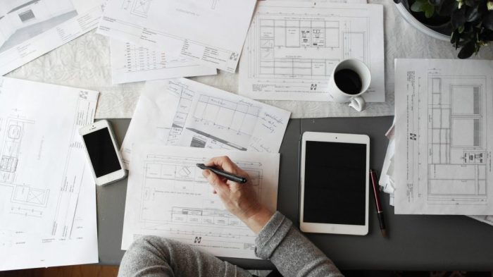 Architect drawing on busy desk.