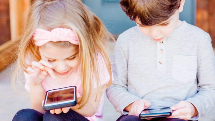 Two small children playing on smartphones.